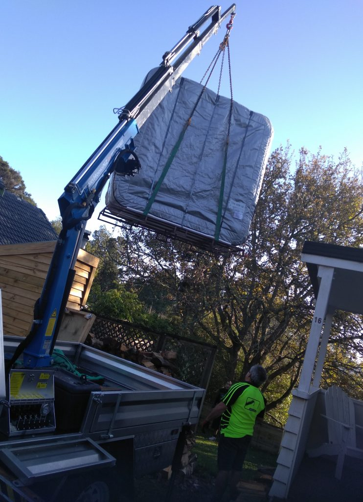 Moving spa over fence with crane